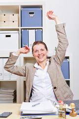 Frau im Büro macht Dehnübungen für den Rücken
