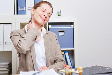 Frau mit Nackenschmerzen im Büro