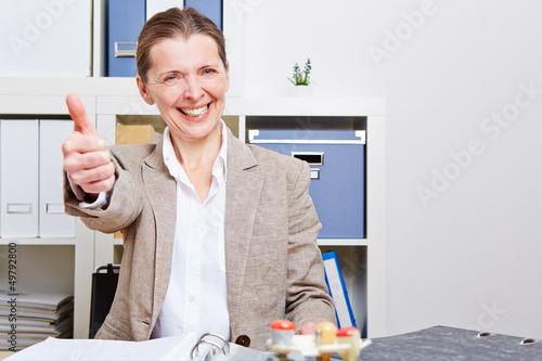 Seniorin im Büro hält Daumen hoch