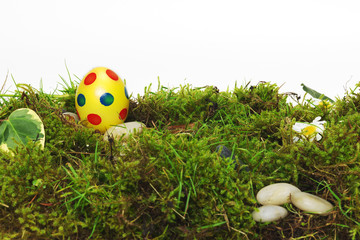 Colorful yellow Easter Egg on moss