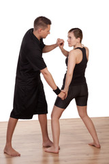 Young man practicing fighting sport with a woman