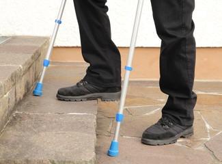 Person mit Kruecken beim Treppensteigen