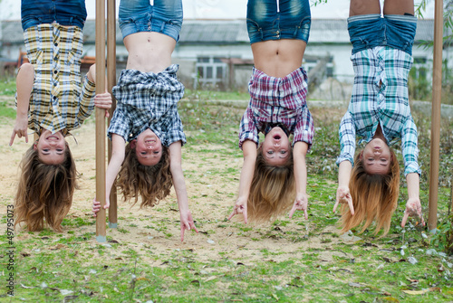 Four young girls hanging upside down in park