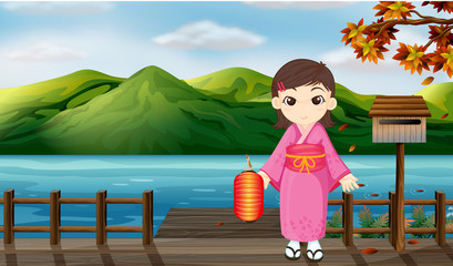 A girl wearing a kimono holding a lantern beside a wooden mailbo