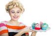 Junge Frau schielt auf Cupcakes im Retro Style und lacht