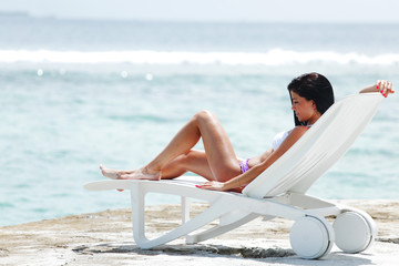 Woman in chaise-lounge near sea