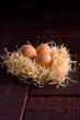 Easter eggs in the basket of hay on a wooden