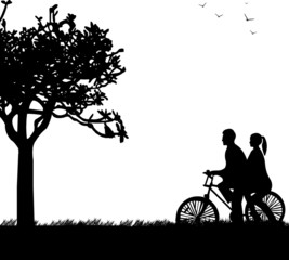 Couple bike ride in park in spring silhouette