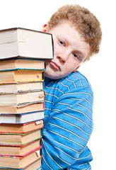 Грустный мальчик выглядывает из за стопки книг