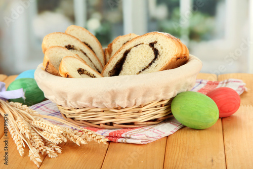 Loaf with poppy seed in wicker basket, on bright background