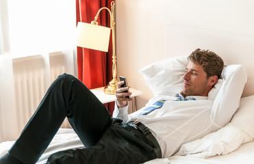 Junger Mann mit Handy, Hotelzimmer, privat, Feierabend