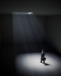 A lonely man standing in a spot of light