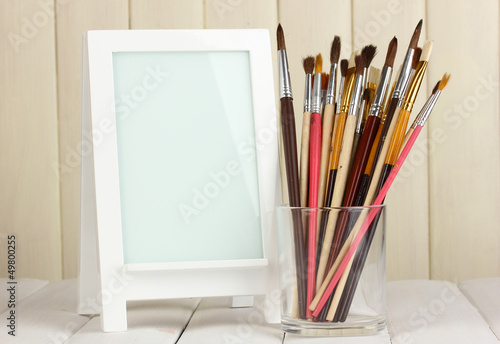Photo frame as easel with artist's tools on wooden background