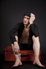 Cute traveler sitting on a suitcase barefoot, thinking, isolated