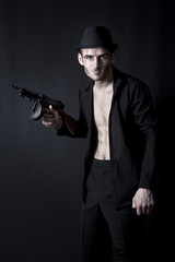Gangster with a tommy gun isolated on black