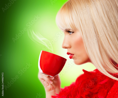 Beautiful blonde young woman with coffee or tea