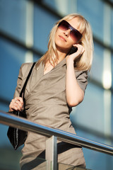 Blond woman calling on the phone against office windows