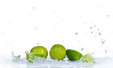 Fresh limes with water splash, isolated on white background