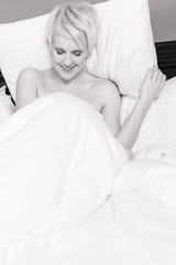 Monochrome image of a smiling woman sitting in a hotel bed