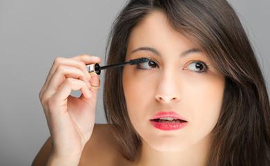Pretty young woman applying mascara using lash brush
