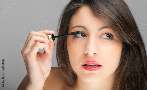 Pretty young woman applying mascara using lash brush