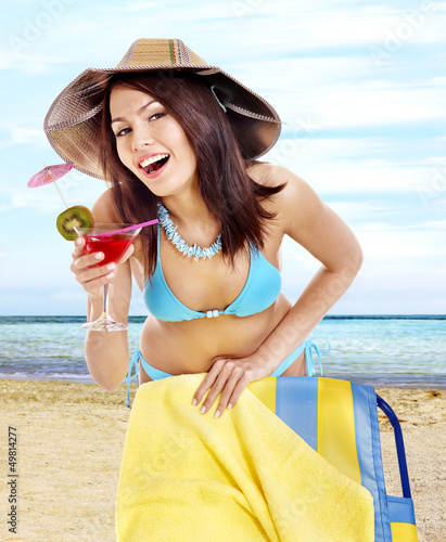 Girl in bikini drink juice on beach.