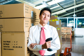 Young Man in a warehouse with Scanner