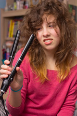 teenage girl with messy hair and flatiron straightener
