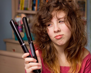 teenage girl with messy hair and flatiron straightener