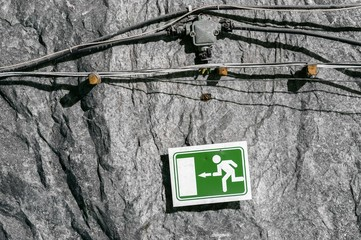 Green exit sign on cave wall