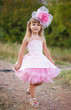 Beautiful little girl in a pink dress walking