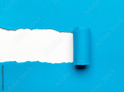 Torn light blue paper with white copyspace