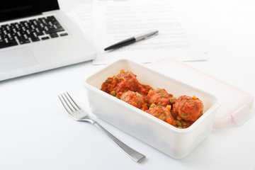 Eating meatballs with tomato in the office
