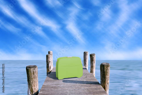 green suitcase parked on the pier