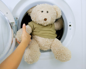 woman taking fluffy toy from washing machine