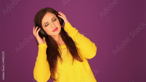 Beautiful woman listening music through headphone
