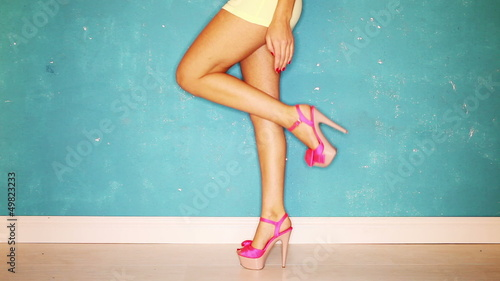 Sexy legs with pink high heels over the blue background
