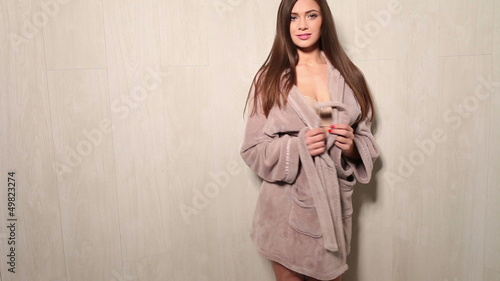 Smiling woman wearing skin toned lingerie with bathrobe