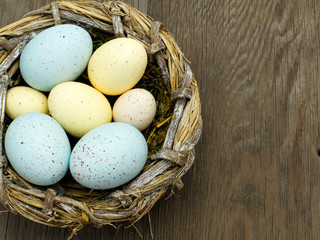 Springtime Easter nest with eggs over a wood background