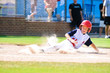Little league baseball player sliding home.