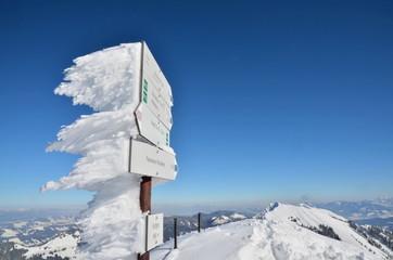 Wegweiser verschneit in Bergen