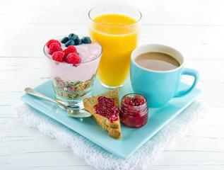 Breakfast with yoghurt, berries, juice, toast and coffee