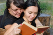 Two close woman friends enjoying a book