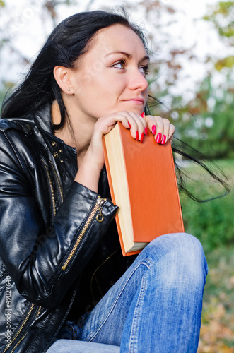 Thoughtful woman with a book