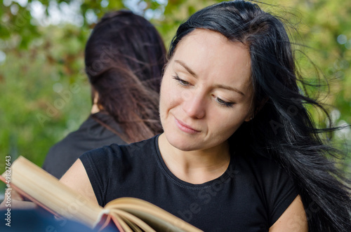Woman smiling as she reads a book