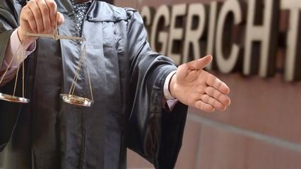 Rechtsanwalt mit Waage vor Gericht mit Handschlag