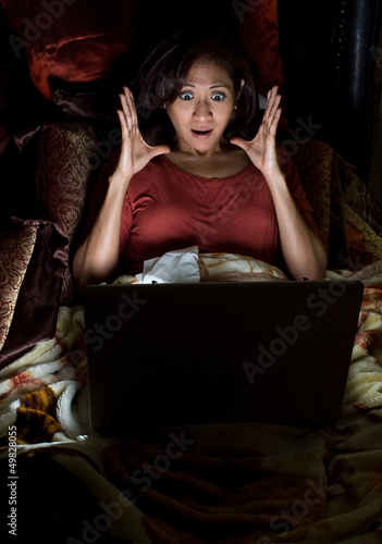 Asian woman having a surprise from her laptop
