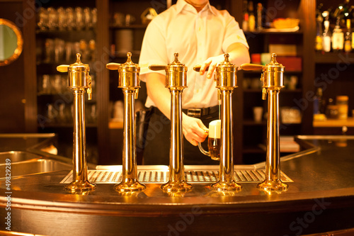 waiter is drafting a beer from a golden spigot
