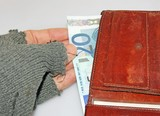 hand of the poor man who steals euro money from wallet