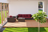 sofa on modern wooden terrace with garden